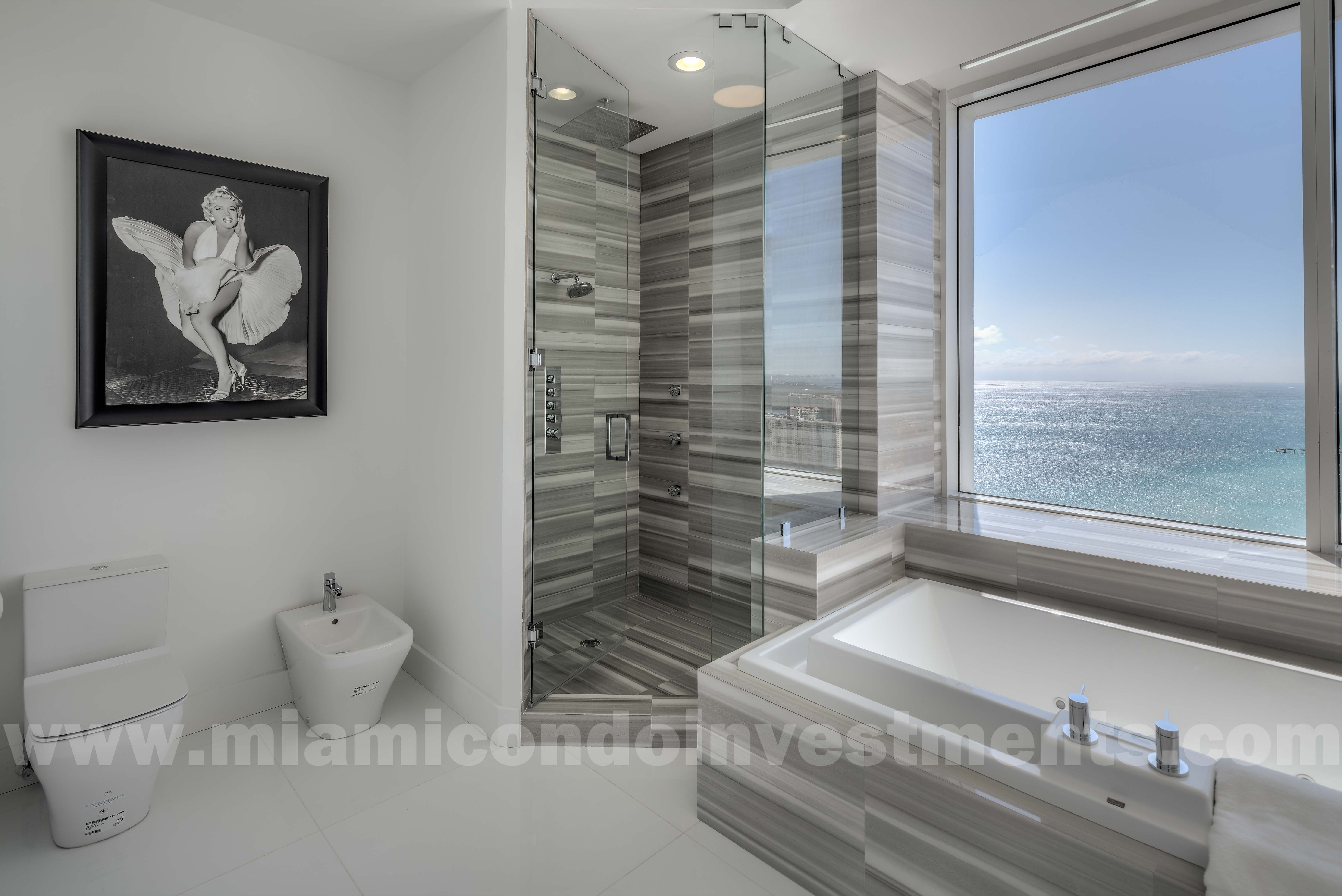 master bathroom with Jacuzzi tub, glass-enclosed shower, bidet, and toilet